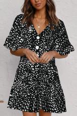 فستان أسود قصير مكشكش بياقة على شكل V مع أزرار